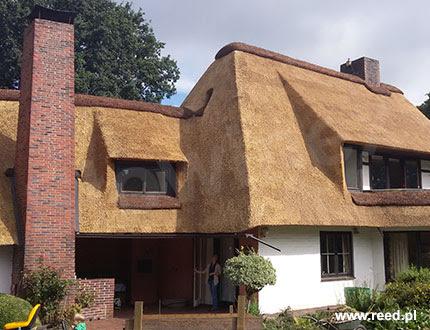 Elegancki biały domek z dużym kominem i pokryciem trzcinowym