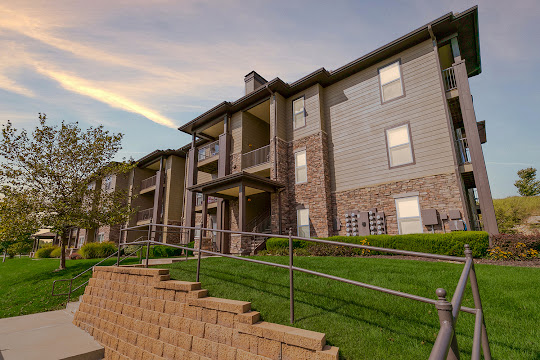 The Dunes at Falcon Valley Apartments brick building with light brown siding at dusk