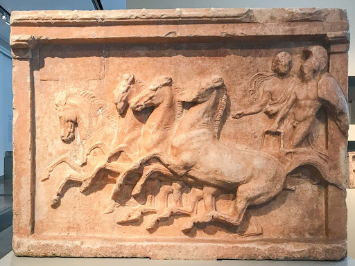 Votive relief for a chariot victory, a marble work from north of Athens, depicts a nude warrior wearing a helmet next to his bearded charioteer. Dates to 390-400 B.C. at the Altes Museum in Berlin.