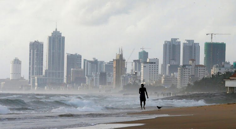 A man walks along a beach, against the backdrop of Colombo's Financial City in Sri Lanka.