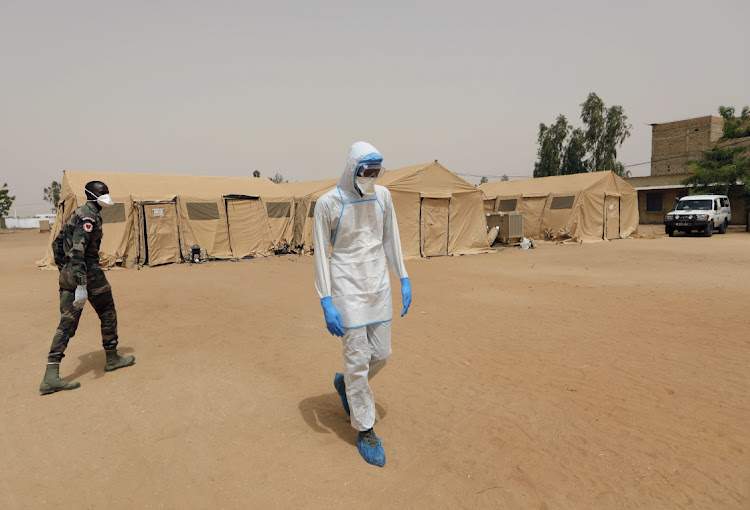 A Senegalese arm doctorwearing personal protective equipment walks towards an isolation tent at the army field hospital in Touba, Senegal. File photo: REUTERS/ZOHRA BENSEMRA