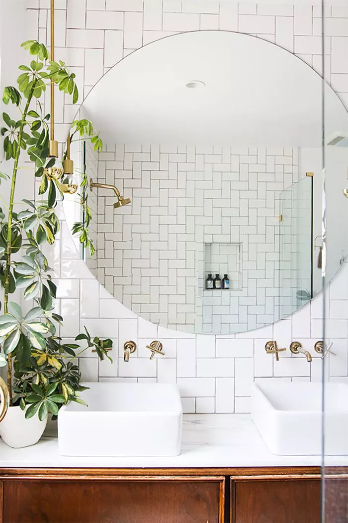 modern bathroom with white subway tile backsplash, large circular mirror, wooden cabinets and small indoor plant