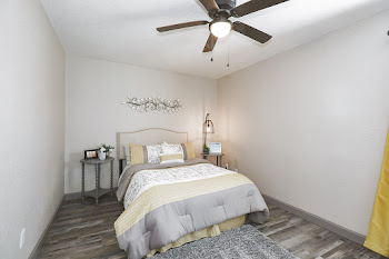 Model bedroom with wood-inspired flooring, light walls, and ceiling fan