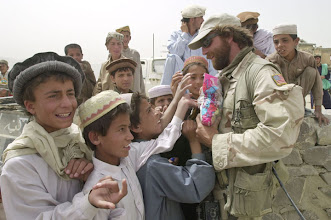 """Photo: ADVANCE FOR STORY SLUG: AFGHAN HAZE OF WAR BYLINE: CHARLES J. HANLEY EIGHT OF TEN PHOTOS  Young Afghan boys surround U.S. Army Sgt. 1st. class """"Victor"""" (only name available) giving out candy during a U.S. organized baseball game Friday, Aug. 16, Urugan Aug. 16, 2002, 193 kms. (120 miles) south of Kabul. Eight months after a lightning victory, U.S. military operations grind on in the swirling dust and heat of the Afghan summer, and in a haze of questions, diminishing returns and growing Afghan unease.(AP Photo/Wally Santana)"""