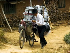 Photo: An peddler pushes his bike full of pots from one village to another.