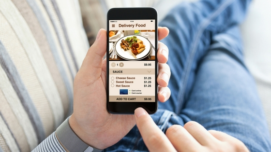 a person holding a smartphone with a food planning app open on it.