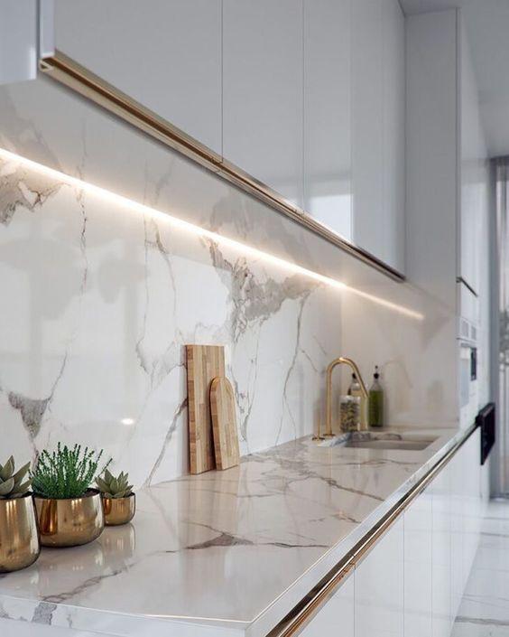 Cozinha com armários brancos com detalhes dourados, parede da pia e bancada revestidas de porcelanato reproduzindo mármore branco e objetos dourados.
