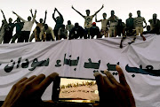 Sudanese demonstrators stand next to banner reading in Arabic