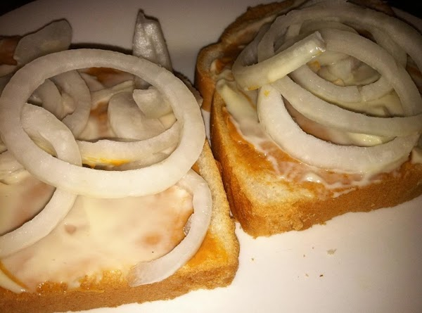 Bread with spread peanut butter, spread mayonnaise and sliced onions.