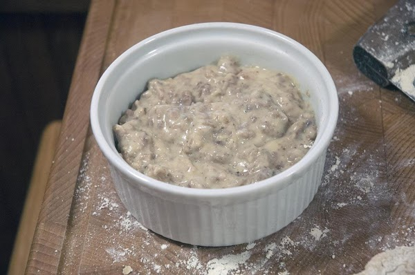 Add some of the sausage gravy to a small ovenproof serving dish.