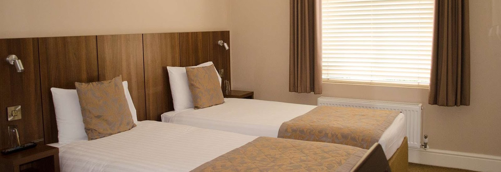 two bedrooms in a hotel room with white bedding and brown throw blankets