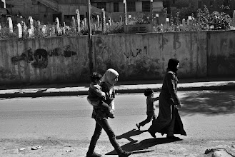 Photo: A family walks the street past a nearby cemetery in the Khaldiya neighbourhood of Aleppo, Syria. Many Syrian refugees who fled the country have recently returned back home due to the high cost of living abroad. Aleppo, SYRIA - 25/4/2013. Credit: Ali Mustafa/SIPA Press