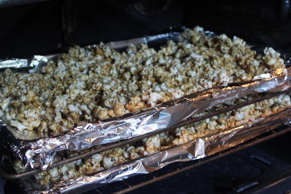 Popcorn on two lined baking sheets in the oven.