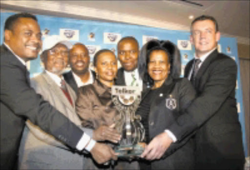 CUP TIED: Mulligan Pearce of Telkom; Leepile Taunyana, life president of the Premier Soccer League and Telkom Charity Trust; Mickey Modisane of Orlando Pirates; Zola Nkutha of Telkom; Sello Nduna of Bloemfontein Celtic; Mphallwa Molepo of Orlando Pirates and Steven Heyward of Telkom captured holding the cup during the Telkom Charity Cup presentation at Summer Place in Rosebank yesterday.Pic. Mbuzeni Zulu. 01/07/08. © Sowetan.
