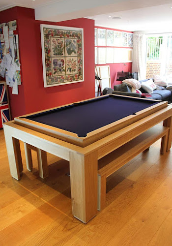 the light wooden spartan pool table with blue felt on a wooden floor in a lounge area