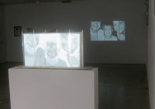 """Photo: """"Labor of Love"""" Fifteen porcelain slabs had small holes of various sizes pressed into them with brass tubes before firing. Collectively, they form a halftone image of my kids, as shown projected in the background."""