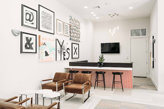 Resident lounge with high top bar, black stools, and wall art