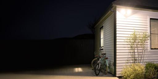 Un projecteur éclaire l'extérieur d'une maison pendant la nuit.