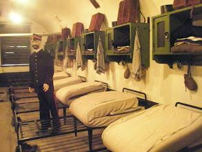 Photo: Slaapzaal tijdens WOI  Let op de lederen soldatenhelmen boven op de kastjes