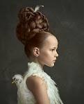 meisje met opgestoken, gevlochten haar en blouse vol kippenveren (kop van kip zit op de rug)