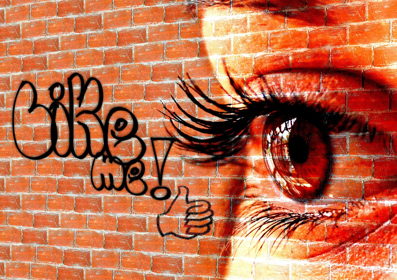 "Translucent brown eye with long lashes over a red brick wall with the spray painted words ""like me!"" and a thumbs up."