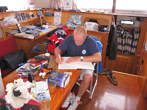 Photo: Andreas writing in the White Admiral guest book in a cabin that really needs tidying up