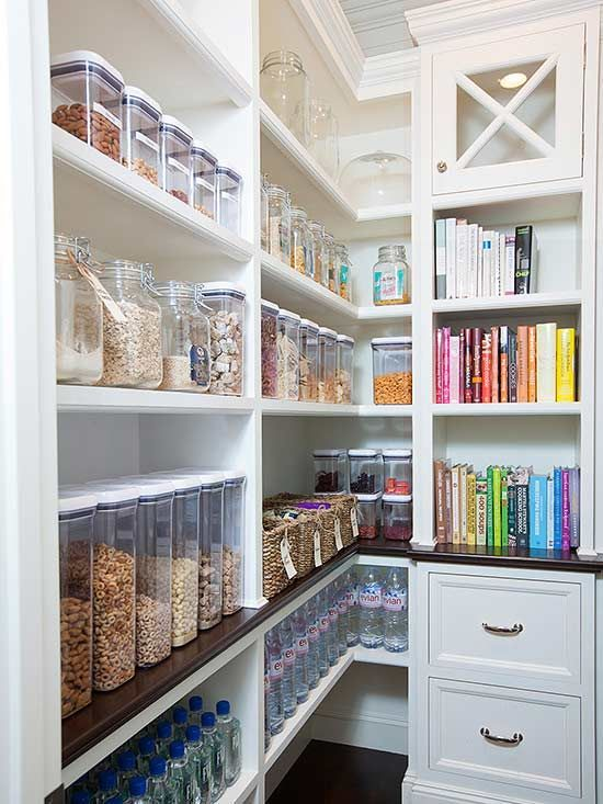 organized walk in pantry idea with glass jars, cookbooks, white pantry cabinets and floor to ceiling shelving