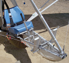 "Photo: The boltaceous construction of the Goat1 is what I call ""garage technology"". With no welding, no machining, no molds, no jigs, no spray rig, it's mostly tubes and cables put together with nuts and bolts. That bulge under a cover flap on the left strut junction is a drogue chute which may be deployed in flight to add drag for short field landings. The red and yellow handle is for the hand deployed emergency parachute, which is rigged to bring down the pilot and glider together, tail first. On the nose tube you can read the aluminum alloy marking, ""6061 T6"", good enough metal but nothing fancy."