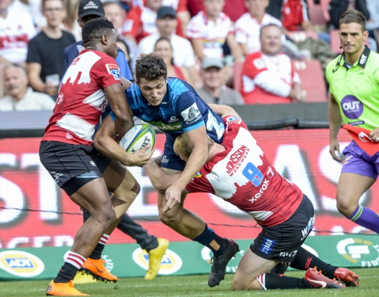 Matt Duffie of the Blues tackled by Aphiwe Dyantyi of the Lions and Ross Cronje of the Lions during the Super Rugby match between Emirates Lions and Blues at Emirates Airline Park on March 10, 2018 in Johannesburg, South Africa.
