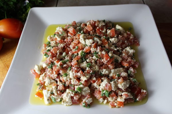 Combine diced tomatoes, green onions, and Feta. Add on top of oil.