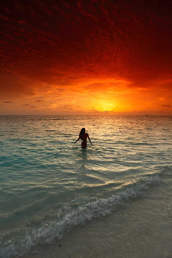 A Cuban woman wades in the surf at sunset.