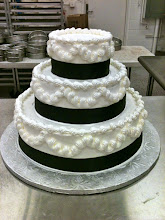 Photo: Classy Wedding Cake: 3-tiers frosted in white, Italian whipped cream. Decor: Lisa's traditional border with black satin ribbon wrapped around bottom of each tier.