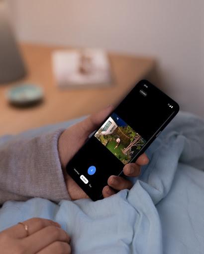 A person checks their phone while sitting inside their home.