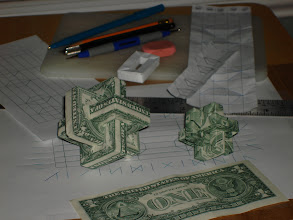 Photo: Behind the dollar Umulius's you can see some of my prototypes - a single plain-paper folded rectangular ring (from a dollar bill sized piece of paper), a small unfolded early prototype crease pattern, and an over-sized older prototype crease pattern.