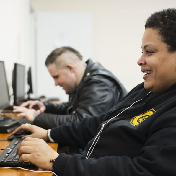 Two young people smiling and working at computers.