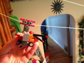Photo: A blurry photo of this early vehicle on the cotton zip line. There was no way to adjust the pitch angle and the bottom pulley was of questionable value.  The cotton thread, while thin, was not as thin as the kite string and also not shiny and slick like the kite string. Vehicles traveled down this line slower. Lego figure with a grappling hook didn't slide at all.    You can see another line in the background, that's the kite string and the preferred line my kids kept going back to.