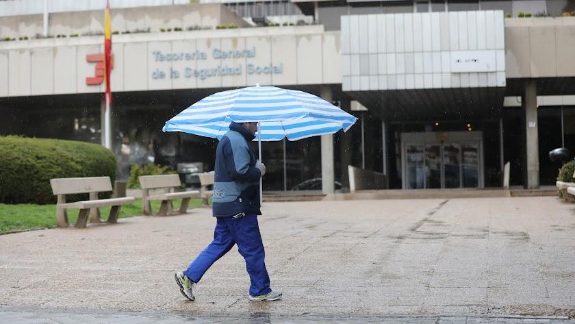 Un hombre con paraguas pasa frente a una oficina de la Tesorería General de la Seguridad Social.
