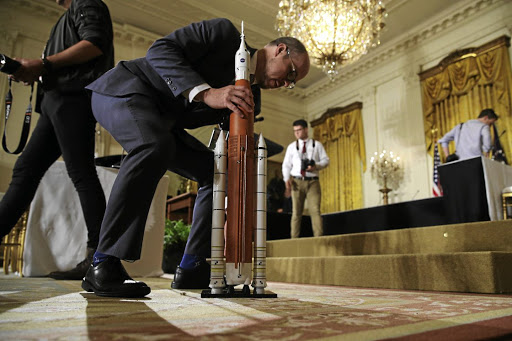 An aide assembles a model of a Nasa rocket as the stage is set for US President Donald Trump to announce his plan for a US space force at the White House on June 18 2018. Picture: REUTERS