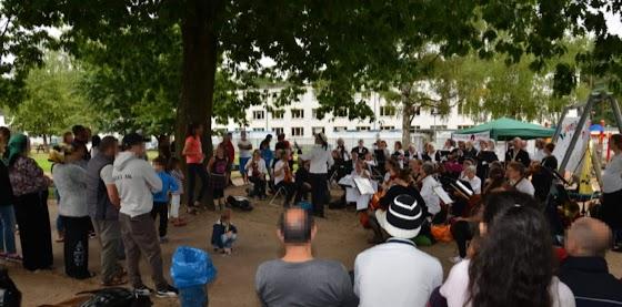 Unterm Kastanienbaum: Orchester und Zuhörer*innen. Im Hintergrund ein Lagergebäude.