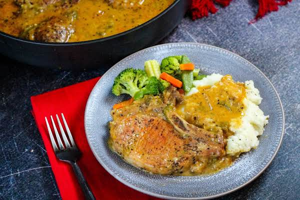 Jamie's Smothered Pork Chops On A Plate With Mashed Potatoes And Vegetables.