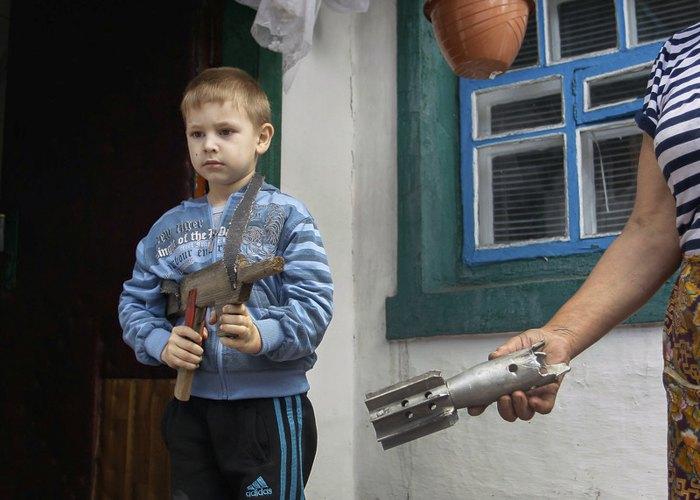 Жінка показує частину снаряда поруч зі своїм зруйнованим будинком після обстрілу бойовиками, села Старомихайлівка недалеко від Донецьку, 24 травня 2016.