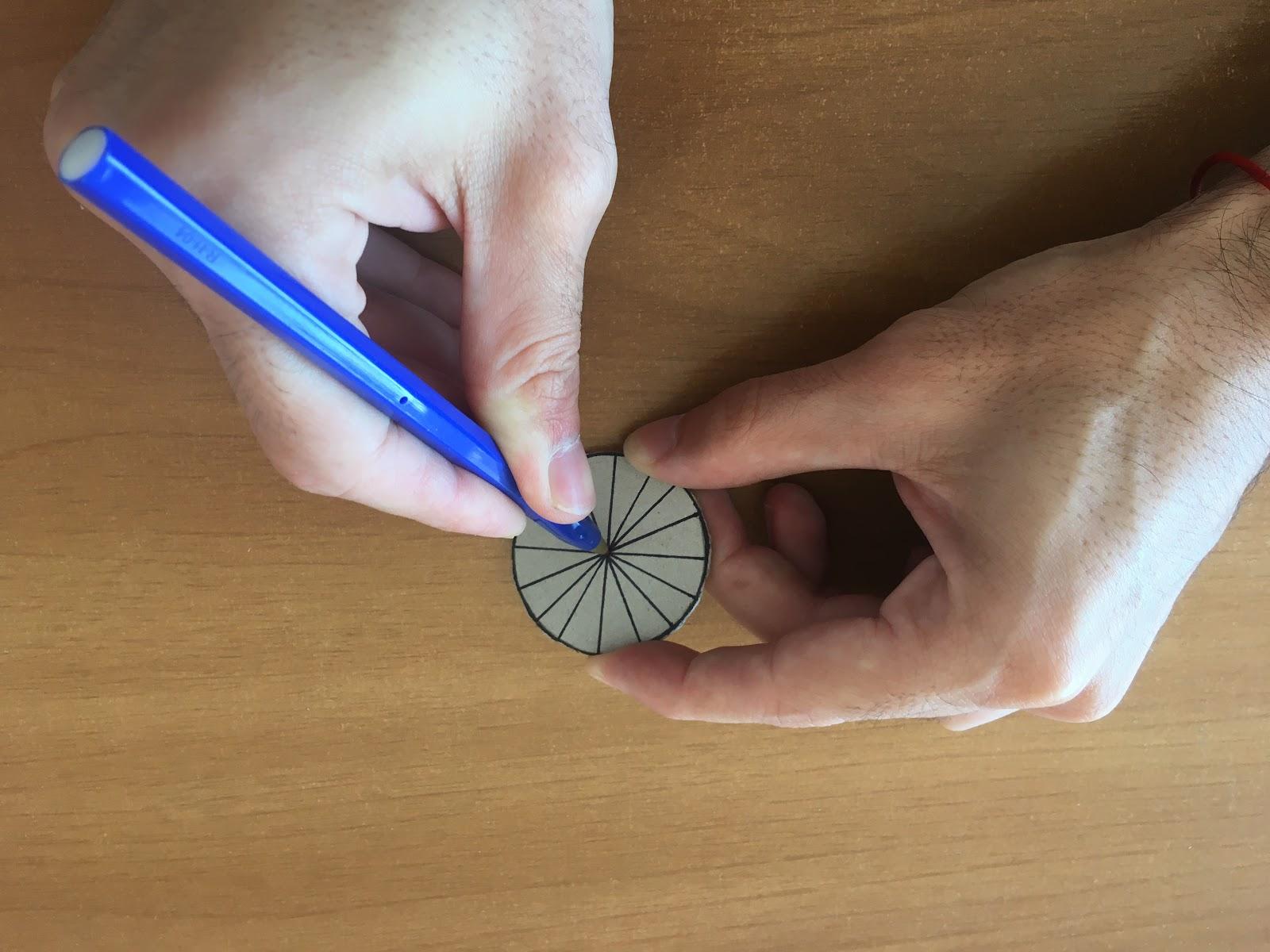 Agujereando la circunferencia de cartón con la punta de una birome.