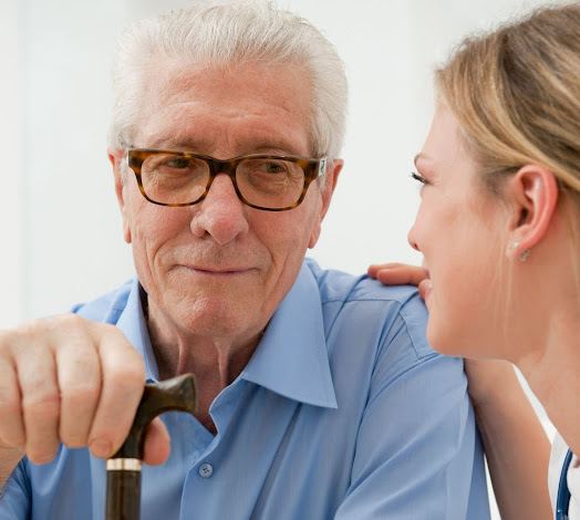 a carer talking to an elderly man in glasses