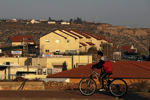 Private property: A boy rides his bicycle past houses in the Israeli settlements of Ofra, in the occupied West Bank. Picture: REUTERS