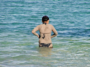 Photo: It is a little hard to distinguish in this photo but this woman is covered with Dead Sea mud which has therapeutic qualities for the skin.