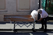 An employee delivers a coffin at the Fondation Rothschild retirement home in Paris, on March 25 2020, where 16 residents have died and 81 have been infected with Covid-19 as the spread of the coronavirus continues in France.