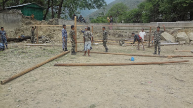 Photo: Locals, army and police personnel helping to build temporary learning centers in the school ground.
