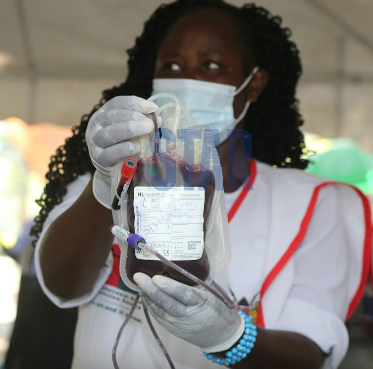 A health worker displays a blood bag during a blood donating exercise held by Kenya National Blood Transfusion Service in partnership with the coalition for blood Africa (CoBA) at Uhuru Park Nairobi on Monday, 8 March. /WILFRED NYANGARESI