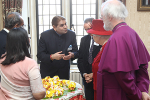 Photo: Bharti Tailor (on left) and the team explain the meaning of Aum to Her Majesty and the Archbishop. Dr. Raj Pandit Sharma, facing (source: archbishopofcanterbury.org)