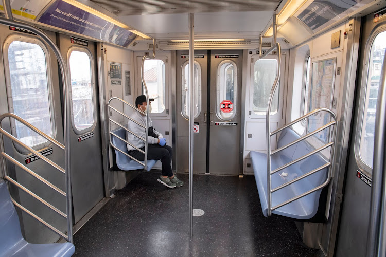 A subway rider wears a mask and gloves in an otherwise empty subway car in New York City during corona outbreak